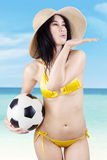 Sexy model with a soccer ball blowing at copyspace Royalty Free Stock Photography