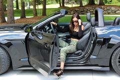 Model in sport car beautiful girl with a Ford mustang Roush stage 3 900 HP horse power muscle car. Beautiful belly, long hair, gorgeous lips and long legs 18 royalty free stock photography