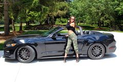 Model in sport car beautiful girl with a Ford mustang Roush stage 3 900 HP horse power muscle car. Beautiful belly, long hair, gorgeous lips and long legs 18 stock photography