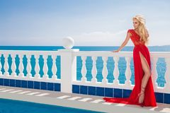 Model wearing a long, red, evening dress, standing by the pool. And luxury hotel and in the background has an amazing view stock images