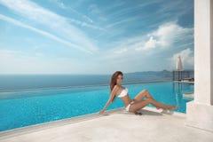 Sexy model in white bikini swimwear. Luxury travel vacation. Bru. Nette Woman sunbathing by infinity swimming pool at luxurious resort. Beautiful destinations Royalty Free Stock Images