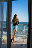Sexy model woman is standing on the balcony with sea on background. View from the hotel room Stock Photography