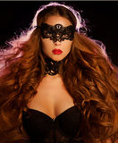 Sexy model woman in venetian masquerade carnival mask. At party over holiday glowing red background. Christmas and New Year celebration. Glamour lady Royalty Free Stock Photos