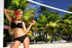 Sexy Modell des blonden Haares mit den festen Hinterteilen und perfekter Zahl, stehend im Bikini und im Hintergrund ist weiße San Lizenzfreie Stockfotos