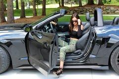 Sexy Modell im schönen Mädchen des Sportwagens mit einem Pferdestärken-Muskelauto Ford-Mustang Roush-Stadiums 3 900 HP Lizenzfreie Stockfotografie