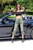Sexy Modell im schönen Mädchen des Sportwagens mit einem Pferdestärken-Muskelauto Ford-Mustang Roush-Stadiums 3 900 HP Lizenzfreie Stockfotos