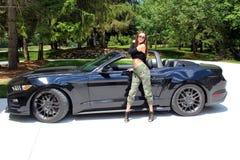 Sexy Modell im schönen Mädchen des Sportwagens mit einem Pferdestärken-Muskelauto Ford-Mustang Roush-Stadiums 3 900 HP Stockfotografie