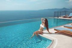 Sexy Modell im weißen Bikini, der durch UnendlichkeitsSwimmingpool ein Sonnenbad nimmt stockfoto