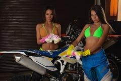 Sexy Modelle, die Motorrad waschen lizenzfreie stockfotos