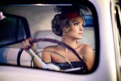 Sexy Modemädchen, das im alten Auto sitzt Lizenzfreie Stockfotografie