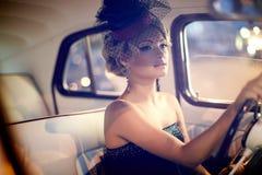 Sexy Modemädchen, das im alten Auto sitzt Stockfoto