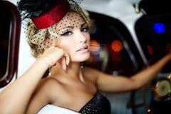 Sexy Modemädchen, das im alten Auto sitzt Lizenzfreies Stockfoto