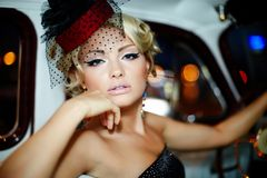 Sexy Modemädchen, das im alten Auto sitzt Lizenzfreies Stockbild