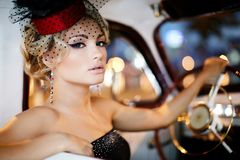 Modemädchen, das im alten Auto sitzt Lizenzfreies Stockfoto