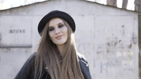 Sexy moderne hipstervrouw in een hoed en een modieus zwart jasje die in een straat dichtbij een uitstekend gebouw blijven actie stock footage