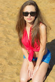 Sexy mooi meisje met lang donker haar die zonnebril dragen die in denimborrels op het strand dichtbij het water op een Zonnige da Royalty-vrije Stock Afbeeldingen