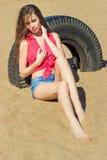 Sexy mooi meisje met lange donkere haarzitting in denimborrels op het strand dichtbij het water op een Zonnige dag Stock Foto's