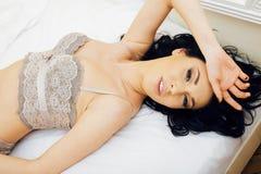 Sexy mooie donkerbruine vrouw die in bed sensuele grijze lingerie liggen, die camera bekijken Verleidingsconcept in luxeruimte Stock Fotografie