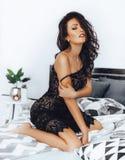 Sexy mooie donkerbruine vrouw in zwarte stock afbeelding
