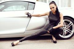 Sexy mooie vrouw met het donkere haar stellen naast luxueuze auto Royalty-vrije Stock Fotografie