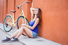 Sexy mooie vrouwenzitting dichtbij de muur en de uitstekende fiets Stock Afbeelding