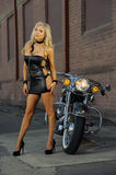 Sexy motorcycle biker girl. Wearing leather dress Stock Photography