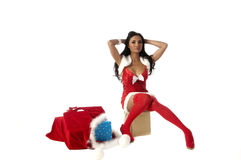 Sexy Mrs Santa. Sexy Mrs. Santa Clause with her bag of gifts at her feet Royalty Free Stock Photography