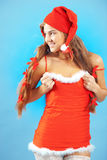 Sexy mrs. Santa. Smiling and posing on blue winter backround Stock Images