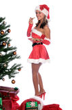 Sexy Mrs. Santa. Sexy Ms. Santa Claus sitting by the Christmas tree with chocolate chip cookies Stock Photos