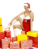 Sexy Mrs. Santa sitting on the gift boxes. Royalty Free Stock Photography
