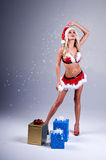 Sexy Mrs Santa With Snow. Sexy blonde dressed as Mrs. Santa in a short fur trimed skirt and bra top blowing snow flakes from her palm and holding a snowball with Stock Photography