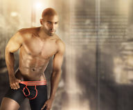 Hot male model. Sexy muscular male model in underwear against modern futuristic abstract background with lots of copy space Royalty Free Stock Photography