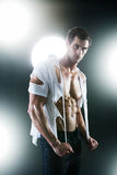 Sexy muscular male in white ripped shirt. In studio Royalty Free Stock Photo