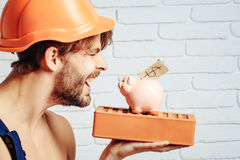 Sexy muscular man builder with moneybox. Young handsome bearded macho man smiling builder with sexy muscular athletic strong body has strong hands in orange hard Royalty Free Stock Photo