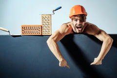 Sexy muscular man builder. Young handsome bearded macho man screaming builder with sexy muscular athletic strong body has strong hands in orange hard hat or Royalty Free Stock Photo