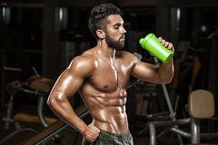 muscular man drinking water in gym, shaped abdominal. Strong male naked torso abs, working out royalty free stock image