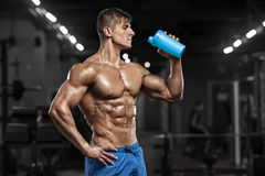 Sexy muscular man drinking water in gym, shaped abdominal. Strong male naked torso abs, working out Stock Images