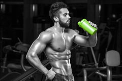 Sexy muscular man drinking water in gym, shaped abdominal. Strong male torso abs, working out.  Royalty Free Stock Photos