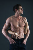 Sexy muscular man and female hands holding his chest Stock Image