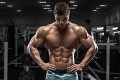 Muscular man in gym, shaped abdominal. Strong male naked torso abs, working out.  royalty free stock image