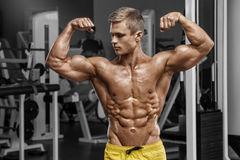 Sexy muscular man in gym showing muscles. Strong male naked torso abs, working out.  Royalty Free Stock Photos