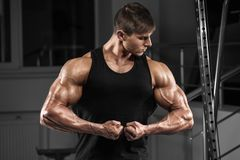 Sexy muscular man in gym, working out. Strong male showing biceps.  Stock Photography