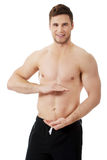 Sexy muscular man holding copyspace in hands. Royalty Free Stock Image