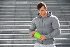 Sexy muscular man holding shaker, outdoors. Young active male drinking water Royalty Free Stock Photo