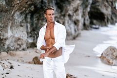 Sexy Muscular Man In A White Shirt With A Bare-chested Resting On The Beach, Ocean Waves At Background. Royalty Free Stock Photos
