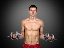 Sexy muscular man lifting dumbbells Stock Photo