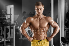 muscular man posing in gym, shaped abdominal. Strong male naked torso abs, working out royalty free stock image