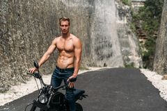 Sexy muscular man riding on motorbike on the road between the rocks royalty free stock photos