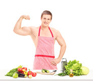 Sexy muscular man wearing a red apron and preparing a salad Stock Images