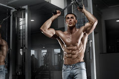 Sexy muscular man working out in gym, shaped abdominal. Strong male naked torso abs Stock Photo